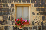Stone house, window and blooming geranium