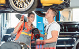 Experienced female auto mechanic with colleague a