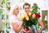 Two women looking at bouquet of roses in flower shop