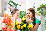 Women in flower store enjoying the roses