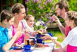Family having coffee time in garden eating cake