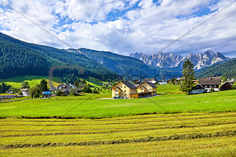 Austrian village among meadows fields and Alpine