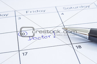 Doctor appointment date writing on calendar.