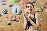 woman climber preparing to climb indoors on climbing gim