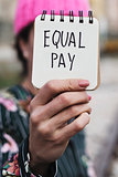 woman with a pink hat and the text equal pay