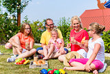 Family having picnic in garden front of their home