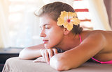 beautiful young woman with flower in hair enjoying her time in tropical spa