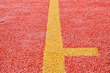 Yellow line on red playing field. Copy space. Sport texture and background