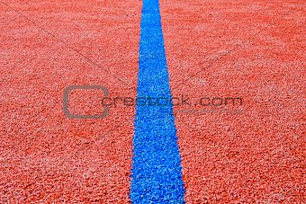 Blue line on red playing field. Copy space. Sport texture and background