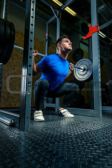 athlete with a barbell in the gym, dark photo