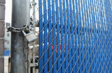 Heavy-duty padlock and chain on blue security gate