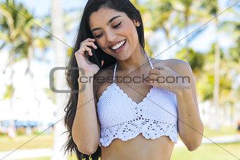 Alluring stylish girl having phone call in park