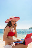 Fashionable young woman talking on mobile phone at the beach
