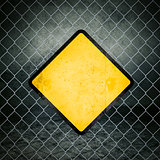 Grunge Yellow Warning Sign on Chainlink Fence of Industrial Ware