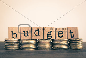 The word Budget on currency, gold coins stack.