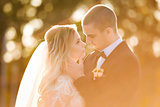 groom is touching bride gently in a sun light