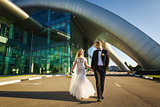 Bride and groom walking near the futuristic building