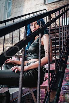 Lovely blue-haired rock girl (informal model), dressed in black leather pants and topic sits on ladder