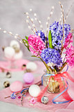 Easter eggs with beautiful hyacinths and willow bouquet on light