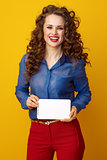happy young woman isolated on yellow background with tablet PC