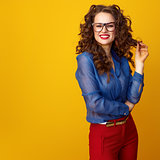 smiling trendy woman isolated on yellow background in glasses