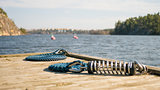Marina wooden deck with blue sailing boat rope for yacht and docking.