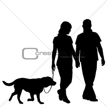 Silhouette of couple taking dog for walk