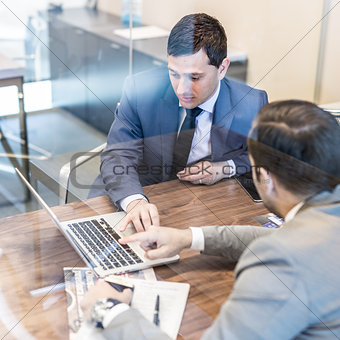 Two young businessmen using laptop computer at business meeting.