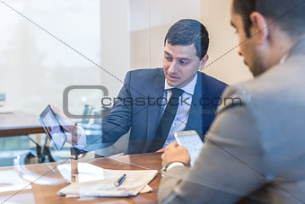 Two young businessmen using electronic devices at business meeting.
