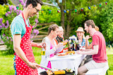 Man grilling meat on garden barbecue party