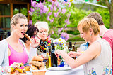Woman eating grilled sausage on bbq party