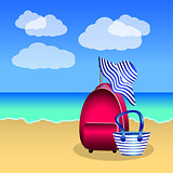 Pink red suitcase, beach bag and hat with blue stripes on the be