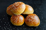 Buns with sesame seeds on a black background