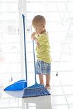 Young kid sweeping floor