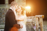 Bride and groom kissing near the lightened by sunset building