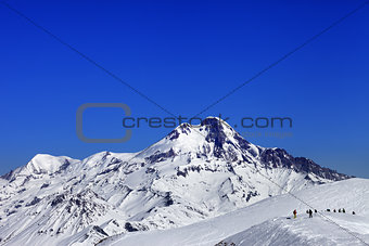 Off-piste slope and mount Kazbek at sun winter day