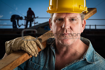 Serious Contractor in Hard Hat Carrying Wood Plank At Constructi