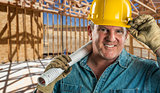 Smiling Contractor in Hard Hat Holding Floor Plans At Constructi
