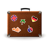Vintage retro suitcase with travel stickers. Old leather luggage bag with stickers of France, Germany, Egypt, UK