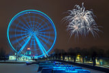 Fireworks explode near the observation wheel at night.