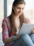 Portrait of Attractive Woman Working on Tablet near Big Window.