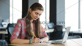 Portrait of a Serious Woman Writing in the Notebook while Working on Laptop lndoors.