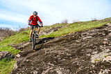 Cyclist in Red Jacket Riding Mountain Bike Down Rocky Hill. Extreme Sport and Adventure Concept.