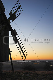 Old wooden windmill by sunset