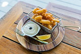 Calamari (Crispy Squid) with sauce and lemon in wooden plate with a fork on the wooden table. Selective focus.