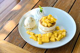 Mango and vanilla ice cream with fluffy cake in white plate on the wooden table. Selective focus.