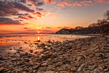 Exciting sunset/sunrise on the rocky coast with water reflection