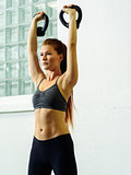 Beautiful young woman lifting kettlebell weights