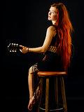 Beautiful redhead woman playing acoustic guitar