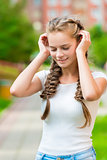 beautiful girl with two braids corrects hands hair, close-up por